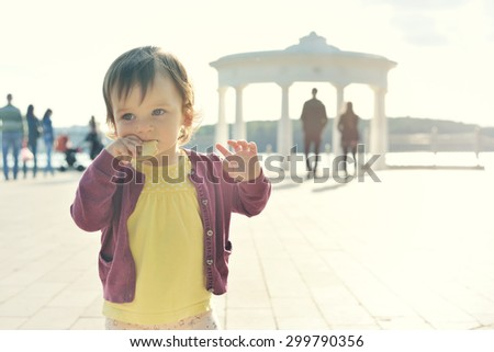 A baby eating biscuit on the background of nature. Child near the lake. Kid walking on the street in the summer. Summer scene with little girl. Summertime, springtime Concept of childhood - stock photo