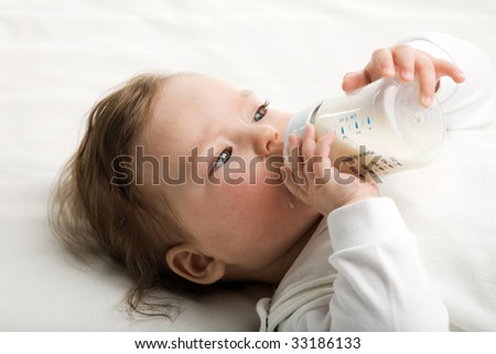 A baby eating milk from the bottle - stock photo