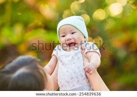 a baby feeling happy and smile widely when she is lifting by her mother. - stock photo