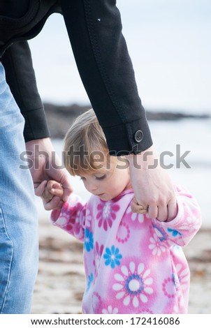 A baby girl holding her father's  hands learning to walk. - stock photo