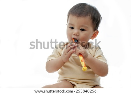 A baby girl is brushing her teeth with a kids' toothbrush, with her two hands holding the toothbrush - stock photo