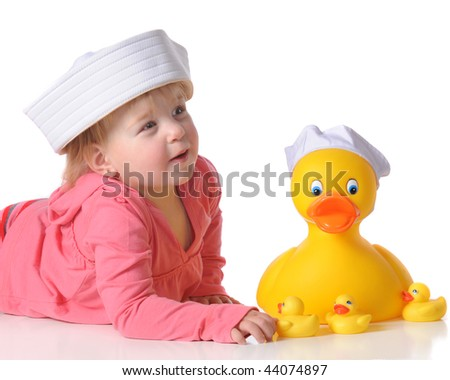 A baby girl playing with a large rubber duck and its ducklings.  Both the baby and the big duck are wearing sailor hats.  Isolated on white. - stock photo