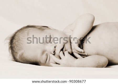 A baby girl sleeping in sepia.