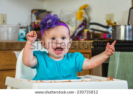A baby girl throws a tantrum in the kitchen - stock photo