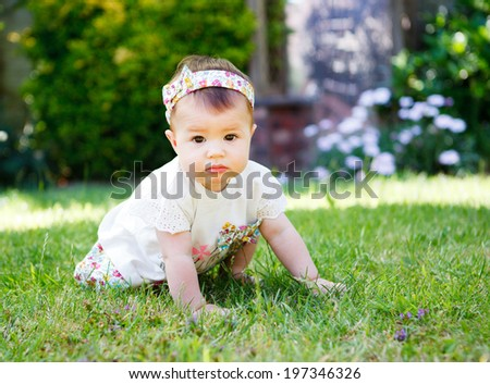 A baby girl with a hair bow crawling on the grass