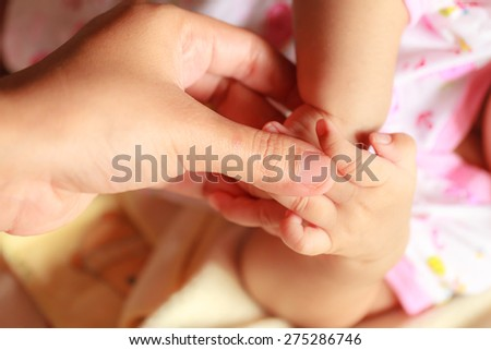 A baby hand in the hand of parent holding - stock photo