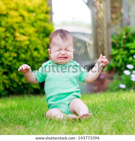 A baby in a green vest sitting on the grass and crying - stock photo