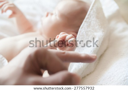 A baby in blanket holding a finger of his parent
