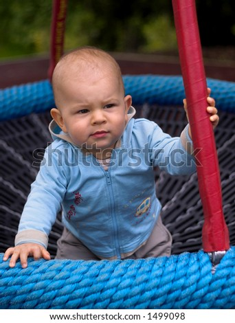 A baby is playing on a playground, he is sitting in a baby-swing. - stock photo