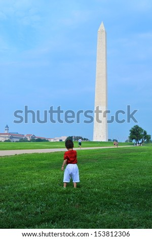 A baby looking upon the Washington Monument - stock photo