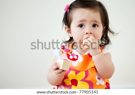 A baby putting child blocks into her mouth with copyspace - stock photo