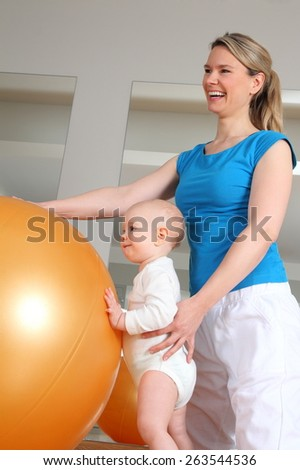 A Baby standing at Physiotherapy beside a Fitness Ball - stock photo