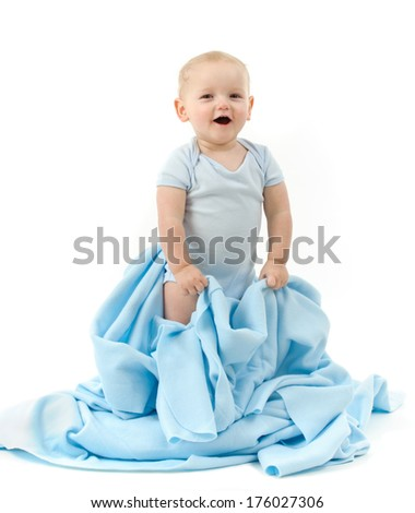 A baby wears blue and stands holding an opened blue sheet. - stock photo