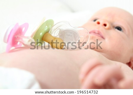 A Baby with diferent orthodontic Pacifiers  - stock photo