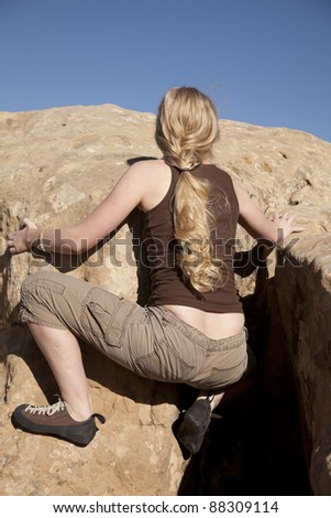 A back view of a woman rock climbing in the outdoors. - stock photo