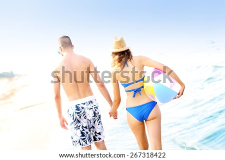 A back view of a young couple walking along the beach - stock photo