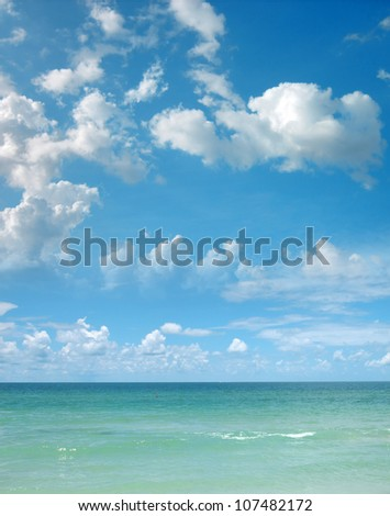 a background image of an open sea and blue sky - stock photo