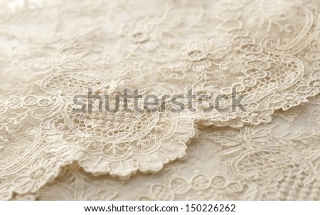 a background image of ivory-colored lace cloth - stock photo