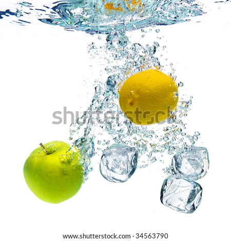 A background of bubbles forming in blue water after ice cubes, lemon and apple are dropped into it. - stock photo