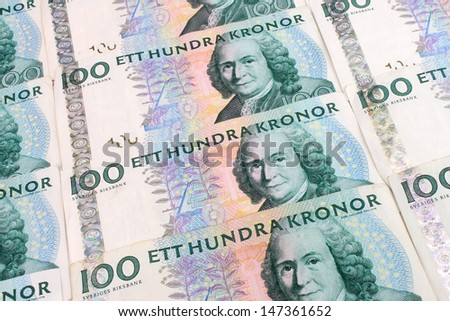 A background of Swedish 100 Kroner currency notes arranged in a grid. - stock photo