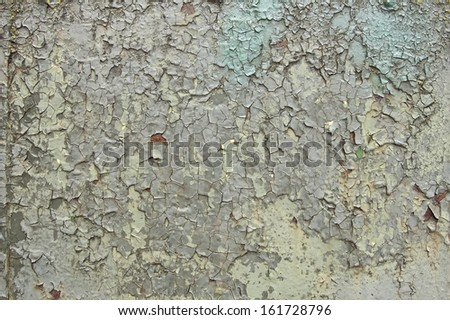 A background texture element with cracked and peeling layers of old paint on rusty steel - stock photo