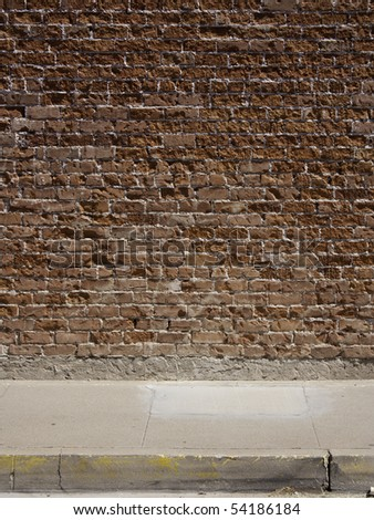 A background texture of a red brick wall and a sidewalk - stock photo