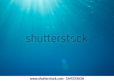 a background with sunbeams underwater - stock photo