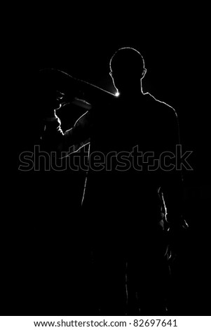 A backlit skateboarder guy posing under dramatic rear rim lighting with his skateboard in black and white. - stock photo