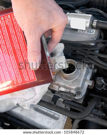 A backyard mechanic pours motor oil into the engine at the end of an oil change - stock photo