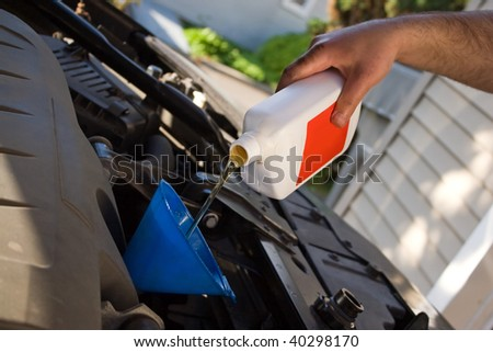 A backyard mechanic pours motor oil into the engine at the end of an oil change.  Home maintenance is becoming more popular during hard economic times. - stock photo