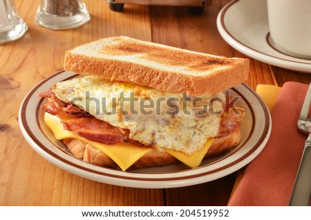 A bacon egg and cheese sandwich with a cup of coffee