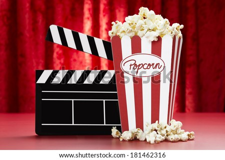 a bag of popcorn and a black cinema clapper board with red background - stock photo