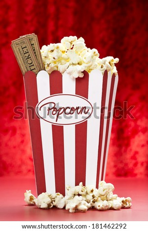 a bag of popcorn and cinema tickets with red background - stock photo