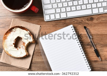 A bagel with cream cheese and a bite taken out next to a computer keyboard and a pad and pen. A cup of coffee in the upper corner, Horizontal for a high angle. - stock photo