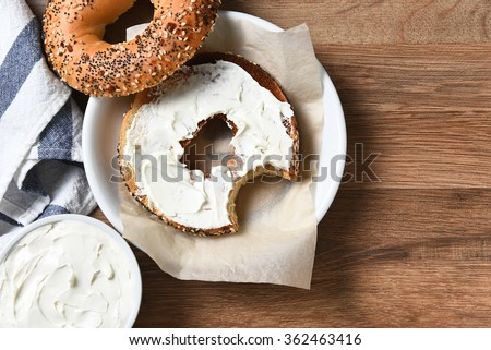 A bagel with cream cheese on a plate and a bite taken out. On a rustic wood table with copy space.