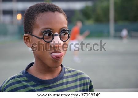 a ball boy takes time out during a tennis match to make faces for his fans - stock photo