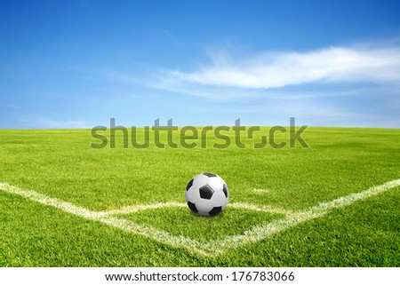 a ball on corner of football field in green grass with blue sky and cloud - stock photo