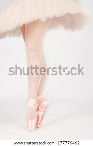 A ballet dancer standing on toes while dancing on peach background artistic conversion - stock photo