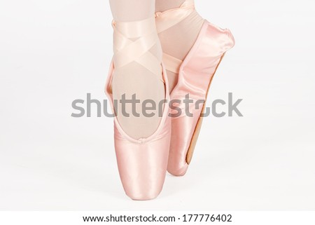 A ballet dancer standing on toes while dancing on white background artistic conversion - stock photo