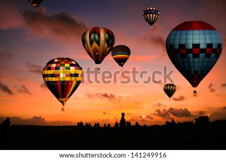 A balloon race at sunrise. - stock photo