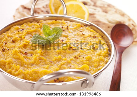 A balti dish filled with tasty Indian dhal or dal, with naan bread and lemon in the background.