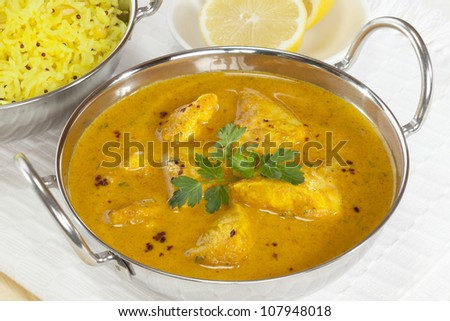 A balti dish with a Peshwari style chicken curry, with basmati rice and lemon in the background.