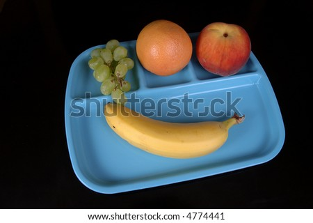 A banana, grapefruit, peach, and grapes on a blue cafeteria tray. Black background.
