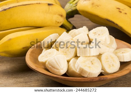 A banch of bananas and a sliced banana in a pot over a table. - stock photo