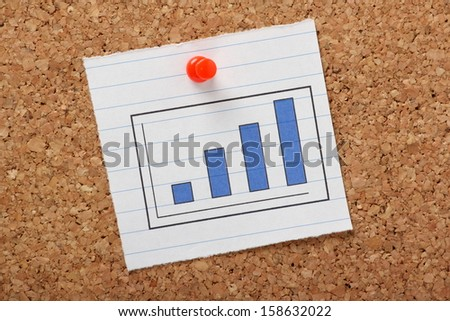 A bar chart or graph showing a positive trend pinned to a cork notice board. - stock photo