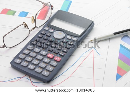 A bar graphs and calculator, pen, glasses on it.