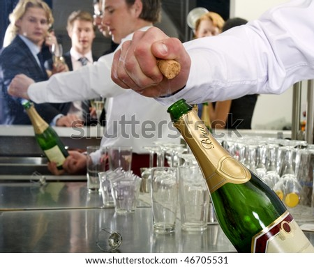 A bar man opening a bottle of champagne behind a bar, with several people reflected in the mirror behind him - stock photo