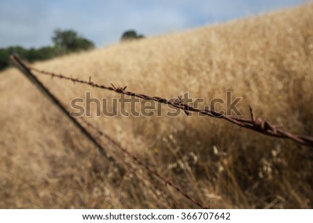 A barbed wire fence stretches across a dry landscape in northern California. - stock photo