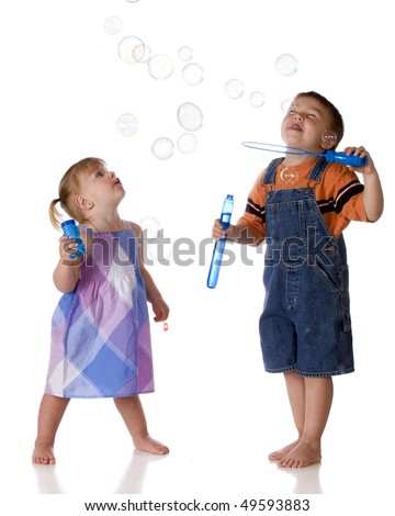 A barefoot preschooler in overalls blowing bubbles for his little sister.  Isolated on white. - stock photo