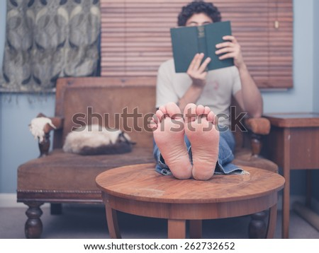 A barefoot young man is resting his legs on a coffee table at home while reading, there is a cat on the sofa next to him - stock photo